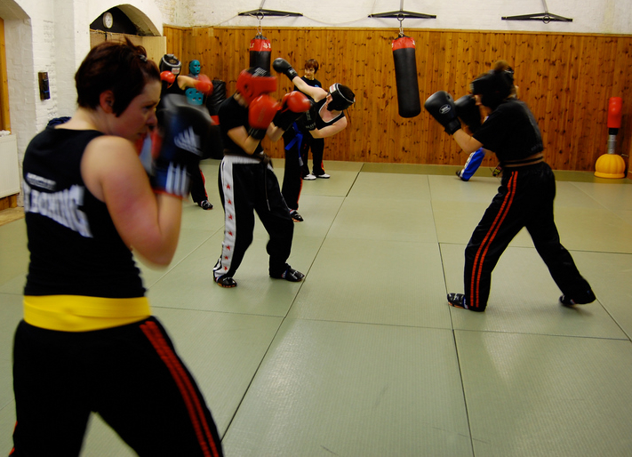 tiffs kick boxing class - women kickboxing sparring in padded helmets